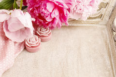 Pink peonies and scented candles on wooden tray Stock Photography