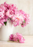 Pink peonies in vase. On wood background Stock Photography