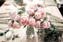 Pink peonies in vase on wooden floor and bokeh background - retro styled photo. soft focus. Pink peonies in vase on wooden floor and bokeh background - retro Stock Photo