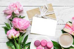 Pink peony flowers and blank greeting card with cappuccino cup, macaroons and gift box on white wooden table