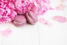 Pink peony flowers with macarons. On a white wooden table Royalty Free Stock Images
