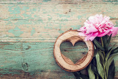 Pink peony and heart carved in wood on the old grunge painted bo Royalty Free Stock Images