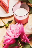 Pink peony and milk in pink glass on wooden table Royalty Free Stock Image