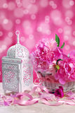 Pink peony in wicker basket and retro lantern Stock Photos