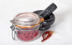 Pink pepper and chili. In a front of a mortar Stock Photography