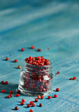 Pink pepper spice on blue background Stock Photos