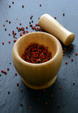 Pink pepper in a wooden mortar Stock Photos