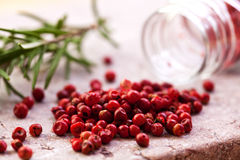 Pink Peppercorns. Closeup of pink peppercorns on a stone background stock images