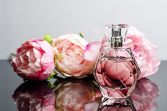 Pink perfume bottle with flowers on black and white background. Perfumery, cosmetics, fragrance collection.  Stock Photography