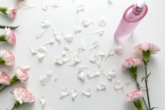 A Pink perfume bottle with pink and white carnation flowers royalty free stock photo