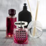 Pink perfumes composition. Two pink fragrance bottles near black big bottle Royalty Free Stock Images