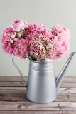 Pink persian buttercup flowers. Curly peony ranunculus in Metallic gray vintage watering can, copy space. Stock Photos