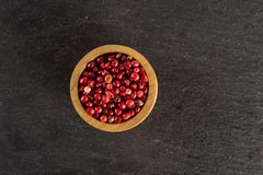 Pink peruvian pepper on grey stone. Lot of whole dry peruvian pink pepper in a wooden bowl flatlay on grey stone stock photography