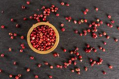 Pink peruvian pepper on grey stone. Lot of whole peruvian pink pepper in a wooden bowl flatlay on grey stone stock images