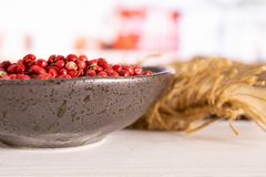 Pink peruvian pepper with kitchen behind. Lot of whole peruvian pink pepper on grey ceramic plate on jute cloth in a white kitchen royalty free stock image