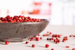 Pink peruvian pepper with kitchen behind. Lot of whole peruvian pink pepper on grey ceramic plate in a white kitchen royalty free stock photography