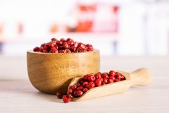 Pink peruvian pepper with kitchen behind. Lot of whole peruvian pink pepper in a wooden bowl with wooden scoop in a white kitchen royalty free stock images