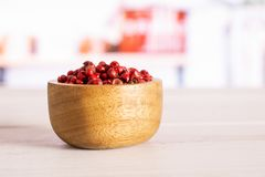 Pink peruvian pepper with kitchen behind. Lot of whole peruvian pink pepper in a wooden bowl in a white kitchen royalty free stock photos
