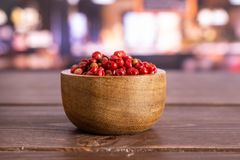 Pink peruvian pepper with restaurant. Lot of whole peruvian pink pepper in a wooden bowl in a restaurant stock photos