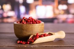 Pink peruvian pepper with restaurant. Lot of whole peruvian pink pepper in a wooden bowl with wooden scoop in a restaurant royalty free stock photo