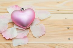 Pink petals and heart on wood. Decoration of pink petals and heart on brown wood with textured background and copy space for text. Top view of flat lay of Royalty Free Stock Image