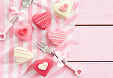 Pink Petit Fours in Heart shape. Colorful petit fours in heart shapes on pink Stock Photo