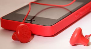 Pink phone or mp player with headphones Royalty Free Stock Images