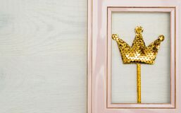 Pink photofrme with golden sequins crown on white wooden backgound. Minimal flat lay with copy space