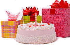 Pink pie with one candle and gifts Royalty Free Stock Photos
