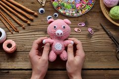 Pink pig. Crochet toy for child. On table threads, needles, hook, cotton yarn. Handmade crafts. DIY concept. Small business. Pink Pig. Crochet toy for child. On royalty free stock image