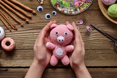Pink pig. Crochet toy for child. On table threads, needles, hook, cotton yarn. Handmade crafts. DIY concept. Small business. Pink Pig. Crochet toy for child. On stock photo