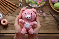 Pink pig. Crochet toy for child. On table threads, needles, hook, cotton yarn. Handmade crafts. DIY concept. Small business. Pink pig. Crochet toy for child. On stock photography