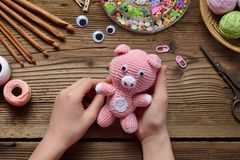 Pink pig. Crochet toy for child. On table threads, needles, hook, cotton yarn. Handmade crafts. DIY concept. Small business. Pink pig. Crochet toy for child. On stock image