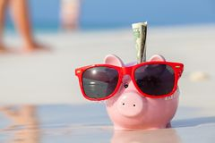 Pink pig moneybox in red sunglasses. On the beach Stock Photo