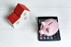 Free Pink Pig Piggy Bank, Calculator And Breadboard Model Of A House With A Red Roof On A Light Background. Concept Of Renting, Buying Royalty Free Stock Photography - 167484077