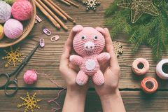Pink pig, symbol of 2019. Happy New Year. Crochet toy for child. On table threads, needles, hook, cotton yarn. Handmade crafts on. Pink Pig, symbol of 2019 royalty free stock images