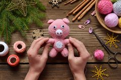 Pink pig, symbol of 2019. Happy New Year. Crochet toy for child. On table threads, needles, hook, cotton yarn. Handmade crafts on. Pink Pig, symbol of 2019 stock photography