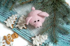 Pink pig, symbol of 2019. Happy New Year. Crochet toy for child. On table threads, needles, hook, cotton yarn. Handmade crafts on. Holiday with your own hands royalty free stock image