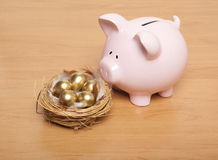 Pink piggy bank. And golden egg in the nest Royalty Free Stock Image
