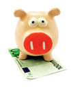 Pink piggy bank. Stands over a cash note isolated on white Royalty Free Stock Photos