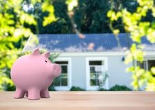 Pink piggy bank against house  door(blurred) Stock Photos