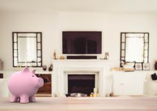 Pink piggy bank against house living room (blurred). Digital composite of pink piggy bank against house living room (blurred Stock Photo