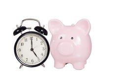 Pink piggy bank alongside an alarm clock Stock Photography