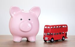Pink piggy bank alongside a red London bus Royalty Free Stock Photo