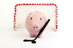 Pink piggy bank with black hockey stick and black hockey puck and red hockey gate with white net on white background Royalty Free Stock Photos