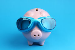 Pink piggy bank with blue swimming goggles on blue background like swimmer Royalty Free Stock Photo