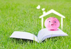 Pink piggy bank on booklet Royalty Free Stock Image