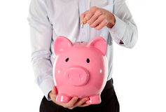 Pink piggy bank with businessman in the background Stock Images