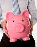 Pink piggy bank with businessman in the background Stock Photography