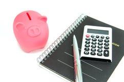 Pink Piggy bank, a calculator. Stock Photo